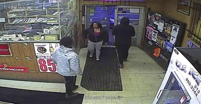 A woman person of interest in the shooting of a teen boy was wearing a black zip up jacket with a burgundy top underneath, gray pants with black and white writing on the leg and black and white gym shoes.
