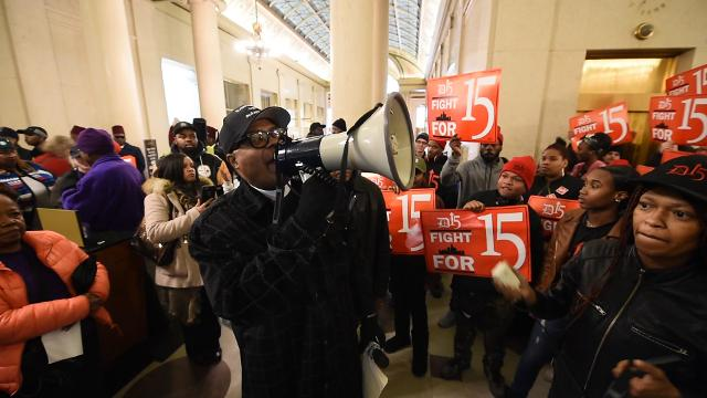Pastor W.J. Rideout III helps lead a rally through the lobby of the state offices in Cadillac Place in Detroit on Tuesday, April 4, 2017.