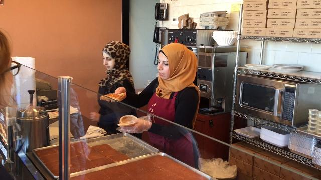 """An employee at Lebon Sweets on Warren makes a """"cheese dome,"""" a sweet square of cheese stuffed inside a freshly-baked sesame bun and brushed with simple syrup."""