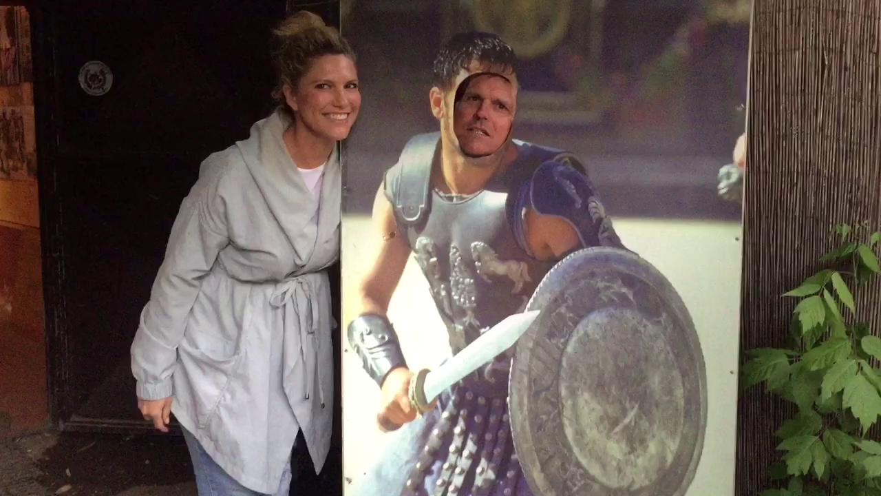 """Michigan coach Jim Harbaugh, with an assist from wife Sarah, recites a scene from the movie """"Gladiator"""" while at Michigan's outing at Gladiator School on Friday."""