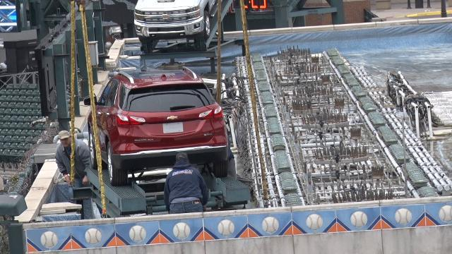 GM cars hoisted up to the Comerica Park fountain