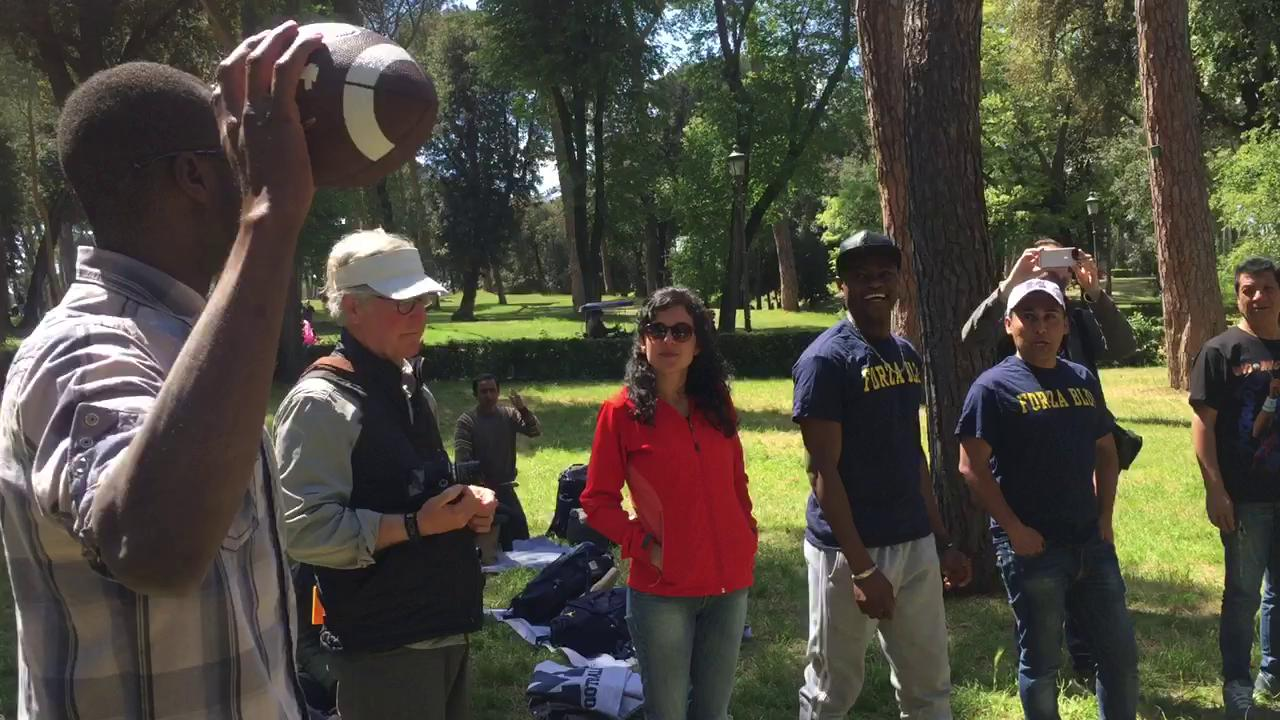 Michigan QB Wilton Speight instructs the refugees the team met on how to throw a football.