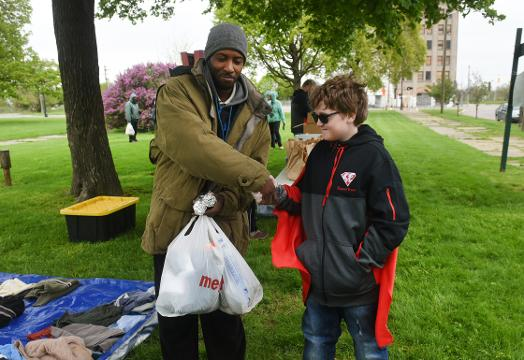 Young volunteer Ewan Baker Drum, 10, hands out food, clothing and necessities to homeless people during the Super Ewan event at Roosevelt Park in Detroit on April 29, 2017.